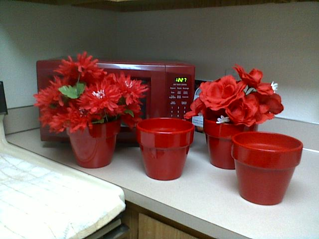 Four red planters 5 1/2 inches high by 6 inches wide at the top